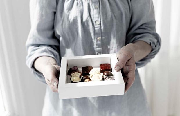 A woman holding a carton board box with chocolates.