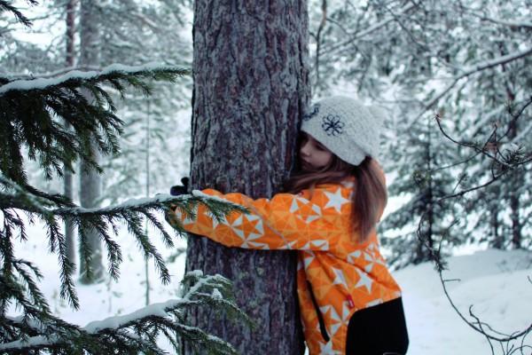 Ett barn kramar ett träd.