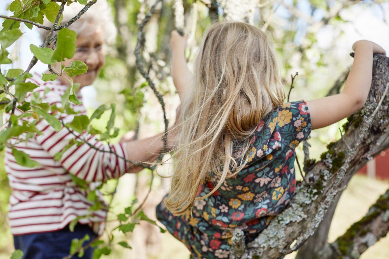 Äldre kvinna och ung flicka som spelar utomhus.
